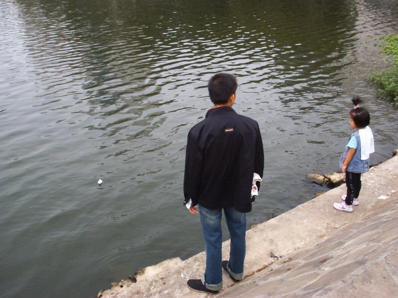 聪儿在湖边看纸船。